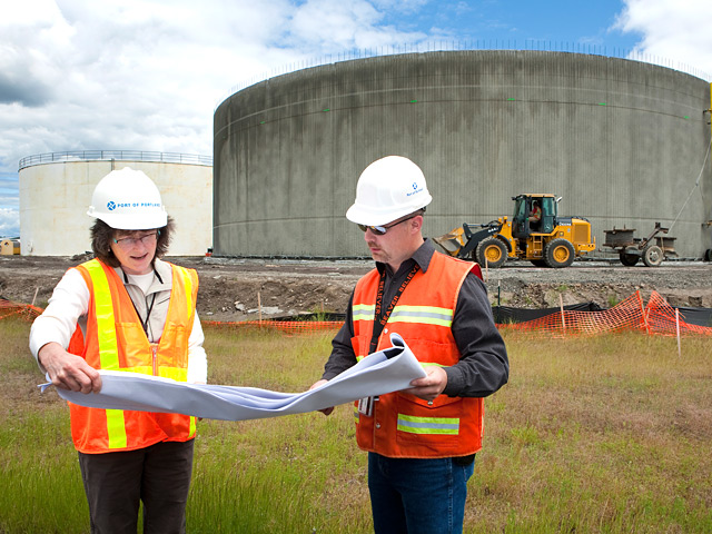 Stormwater containing deicing material at PDX is collected in storage tanks.  The new tank behind Craig Redlinger, construction manger, and Susan Aha, evironmental manager, will hold three million gallons of stormwater collected from around the ariport terminal building and aircraft parking areas.