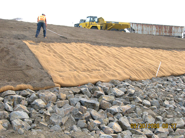 Wheeler Bay: Contractor raking topsoil over the jute matting transition area.