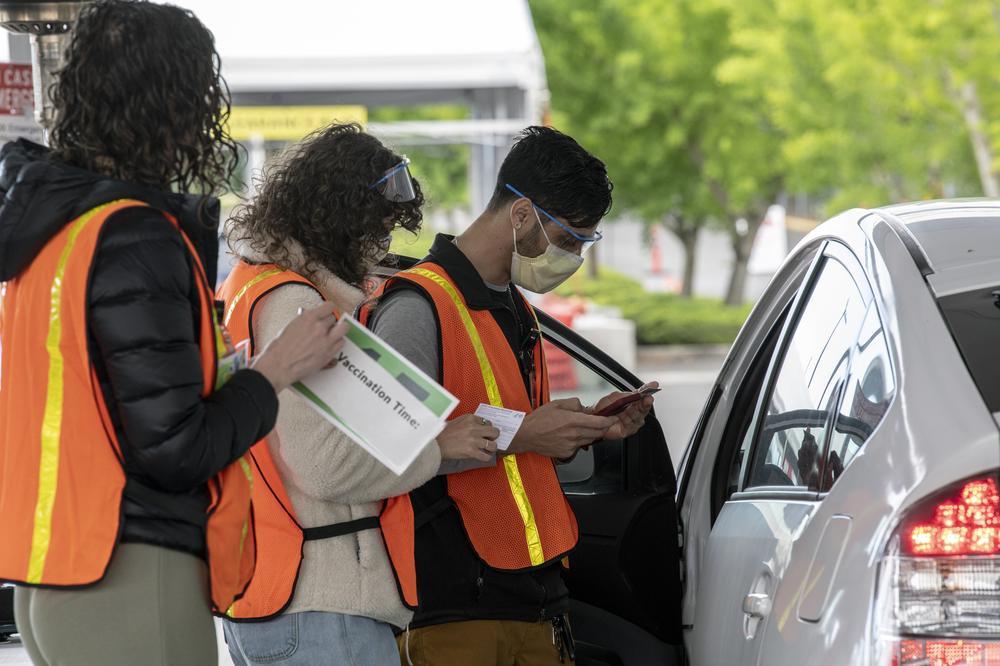 Three OHSU staff members in orange safety vests talk to a vaccine recipient in their vehicle