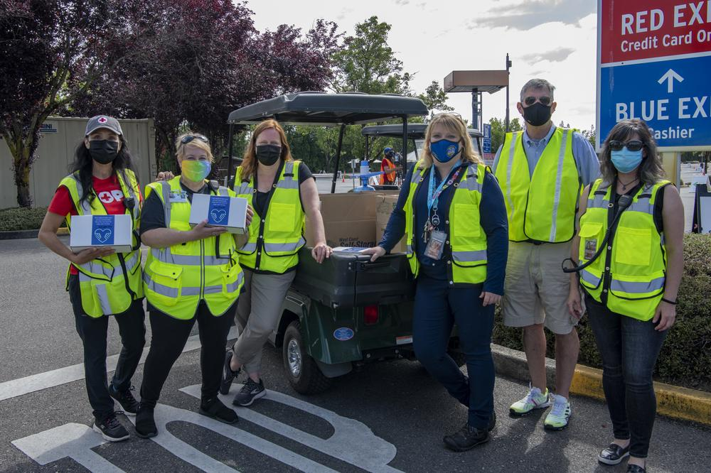 Six staff members from the Red Cross, OHSU, and Port of Portland stand and pose for a photo at the Red Lot vaccine clinic.