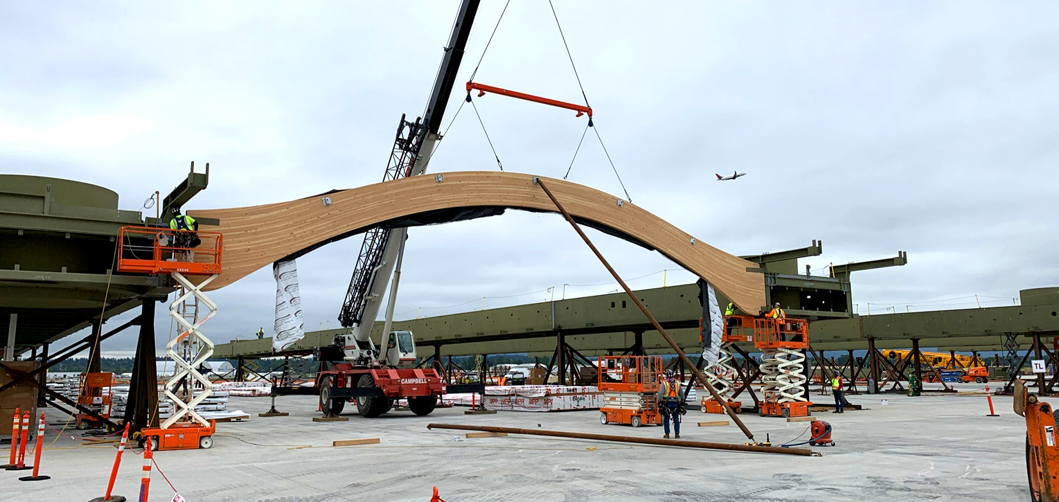 A crane helps slide a curvy beam into a segment of the new roof